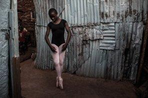 Pamela is practicing Ballet outside her family's house in Kibera.