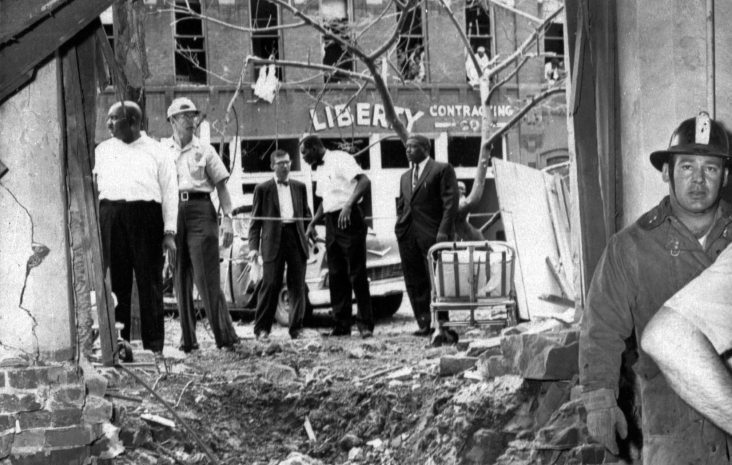 ADVANCE FOR USE SUNDAY, AUG. 25, 2013 AND THEREAFTER - FILE - In this Sept. 15, 1963 file photo, emergency workers and others stand around a large crater from a bomb which killed four black girls in the Sixteenth Street Baptist Church in Birmingham, Ala. The windows of the building across the street in the background were also blown out. (AP Photo)