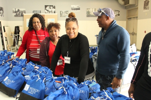 The BIZZ Magazine's founder Octavia Clayton Smith with husband Vernon and several volunteers preparing for bag giveaway.